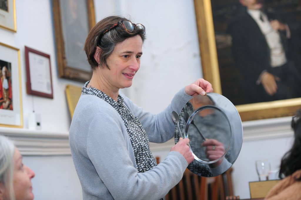 A Citizen Curator creating music by hitting a silver plate with a spoon during the interpretation session.