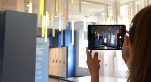 The featured image for the wAVE page is a woman viewing a museum through a tablet.