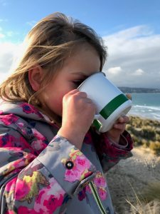 A young girl in a pink coat lifts up a metal mug to her face, drinking. Behind her is a bright blue sky and glimpses of a beach.