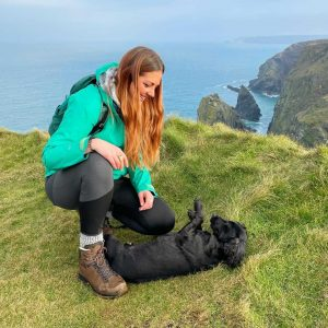 A young woman in hiking gear kneels down on the grass next to a small, black dog rolling on the floor. Behind them is a view over some Cornish cliffs across to the sea.