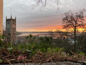 A landscape photograph of a Falmouth sunrise - on the right is the church tower and to the left views over the River Fal and the orange clouds in the sky.