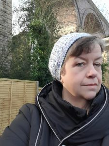 A selfie of a woman wearing a grey hand-knitted hat, behind her is an archway and trees.
