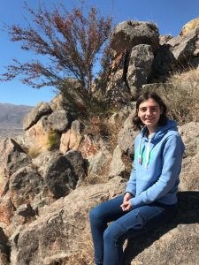 A young woman in a blue jumper and jeans sits on a rocky outcrop in a sunny desert environment.