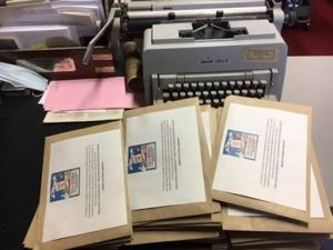 A stack of envelopes in front of an old fashioned typewriter. Each envelope has a printed label on the outside with text on it (too small to read).