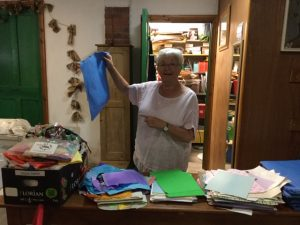 A volunteer holds up an activity pack and points to it with her other hand, smiling at the camera. Before her is a table full of piles of papers and craft supplies to be made into more packs.