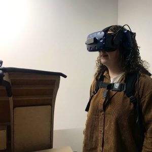 A young woman in a brown shirt stands to the right of the image, inside a white room. She is wearing a black VR headset and looking straight ahead to the side.