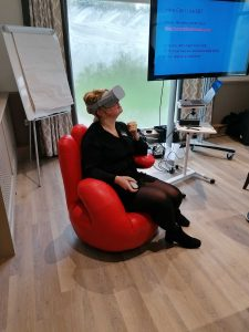 A woman dressed in black sits in a red chair and looks around her wearing a grey VR headset.