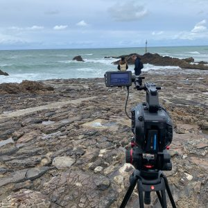 A black camera on a tripod is in the foreground, before it is a rocky coast and blue sea somewhere in Cornwall.