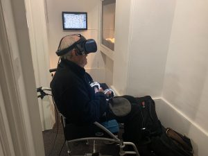 An elderly man in a wheelchair looks around while wearing a black VR headset.