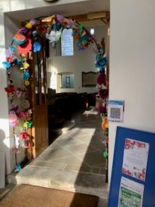 A colourful, handmade paper flower arch is nestled in the doorway of St Michaels Church.