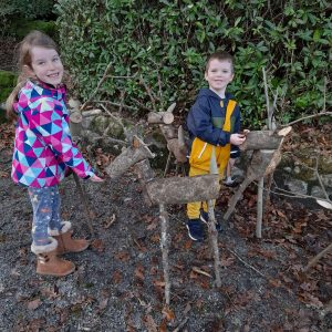 Two young children, a girl and a boy, smile up at the camera. They are stood outside in the mud next to two wooden reindeer sculptures.