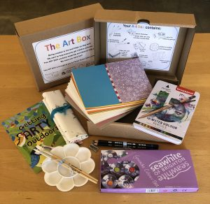 An array of crafting items laid out on a table in front of a cardboard box labelled 'The Art Box'. The items include a sketchbook, colouring pencils, paints, paintbrushes, palette and 'Getting Art Outdoors' booklet.