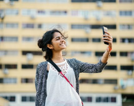 A young woman in an urban outdoor setting holds up her phone and smiles to take a selfie.