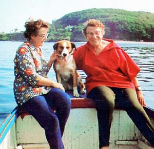 An aged photograph of two women sat at the back of a boat with a dog between them. Behind them is a sunny Cornish coastal view.