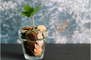 A stock image showing a glass full of pennies with a small shoot growing out.