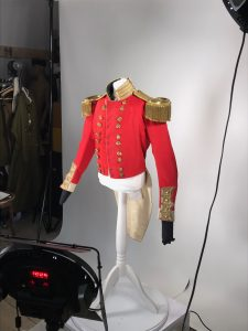 A red and gold military costume on a stand is being photographed with a white screen and lights around it - part of the digitisation capture process at Bodmin Keep.