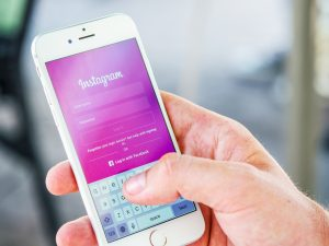 A hand holds up a white iPhone, typing in their log in details on the Instagram social media home page.