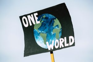A wooden placard bearing a black poster with a painting of the globe on it reading 'ONE WORLD'.
