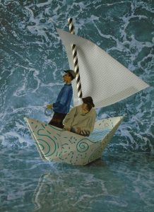 A paper creation of two figures in a sail boat.