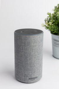 A grey Amazon Alexa smart speaker on a white table.
