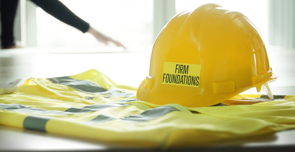 A yellow hard hat and neon gilet sit on a table; the hat bears a sticker reading 'FIRM FOUNDATIONS'