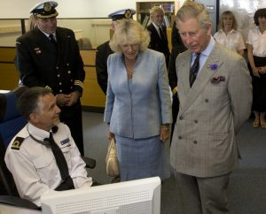 Prince Charles and Camilla stand on the right facing towards the camera, as they look down at a computer screen. A man (Henry) in a naval uniform sits before the screen and looks towards them.