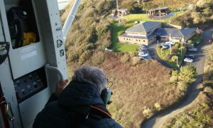 An aerial picture taken from inside a helicopter, showing a mean looking down towards Falmouth Coastguard Station.