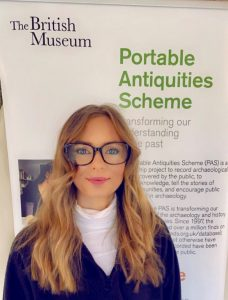 A young woman wearing glasses and with long blonde hair stands before an exhibition board which reads 'Portable Antiquities Scheme'