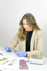 A young woman sits at a white desk and handles archaeological finds.