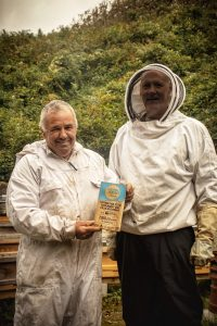 Two men in beekeeper outfits smile and hold a blue Cornwall Heritage Awards trophy.