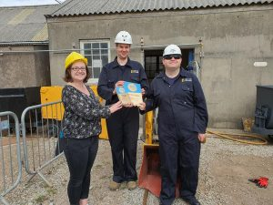 A woman wearing a yellow hardhat presents blue Cornwall Heritage Award trophies to two young men in navy boilersuits and white hardhats.
