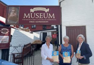 Three women stand before a large museum exterior, with a sign reading 'Mevagissey and District Museum'. They are smiling and holding two blue Cornwall Heritage Awards trophies.